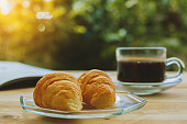 Croissants, a cup of coffee and opened book on blurred green natural background, selective focus and vintage retro color