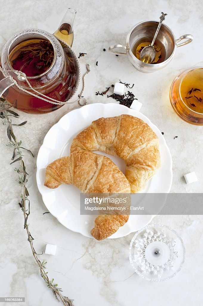 Croissants, honey and tea on table : Stock Photo