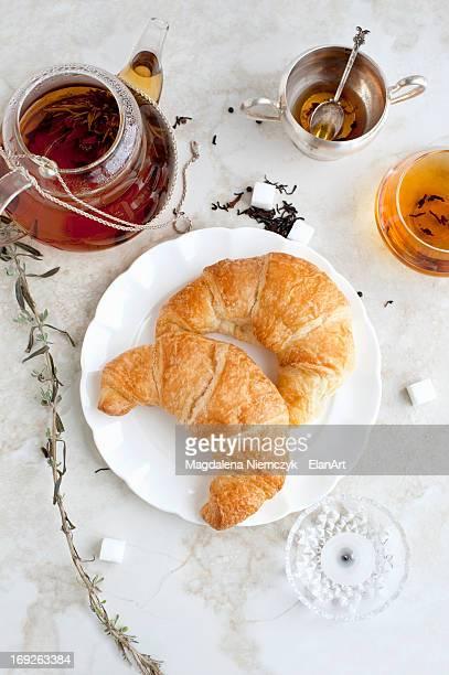 Croissants, honey and tea on table