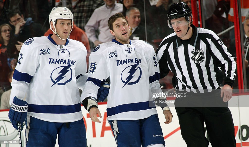B.J. Crombeen #19 of the Tampa Bay Lightning is helped off the ice by teammate Eric Brewer #2 and Linesman Matt MacPherson #83 after fighting Zac Rinaldo #36 of the Philadelphia Flyers (not pictured) on February 5, 2013 at the Wells Fargo Center in Philadelphia, Pennsylvania.