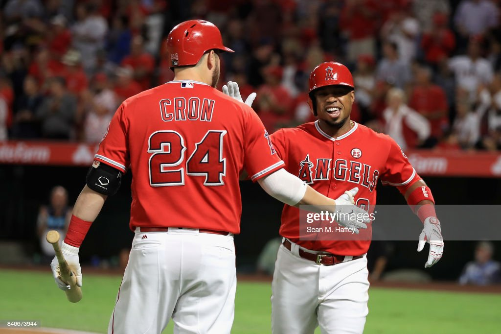 C.J. Cron #24 congratulates Luis Valbuena #18 of the Los Angeles Angels of Anaheim after his two-run homerun during the first inning of a game against the Houston Astros at Angel Stadium of Anaheim on September 13, 2017 in Anaheim, California.