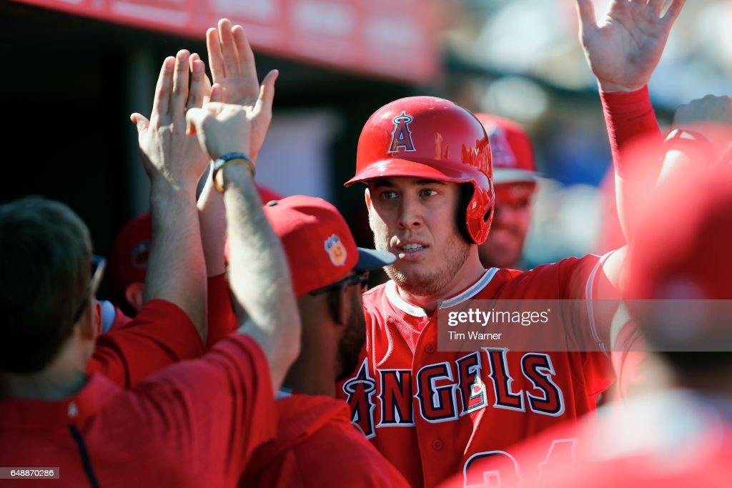 C.J. Cron #24 of the Los Angeles Angels is congratulated by teammates in the dugout after scoring in the third inning against the Chicago Cubs during the spring training game at Tempe Diablo Stadium on March 6, 2017 in Tempe, Arizona.