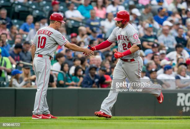 J Cron of the Los Angeles Angels of Anaheim is congratulated by third base coach Ron Roenicke as he rounds the bases after hitting solo home run off...