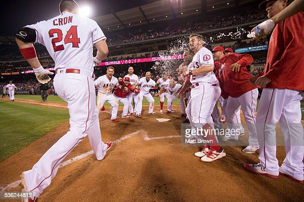 J Cron of the Los Angeles Angels of Anaheim is greeted at home plate by his teammates after hitting a walkoff tworun home run to defeat Detroit...