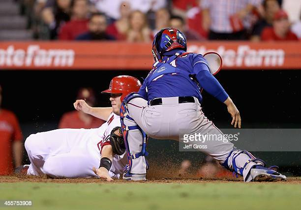 J Cron of the Los Angeles Angels of Anaheim is tagged out at home by catcher Robinson Chirinos of the Texas Rangers in the seventh inning at Angel...