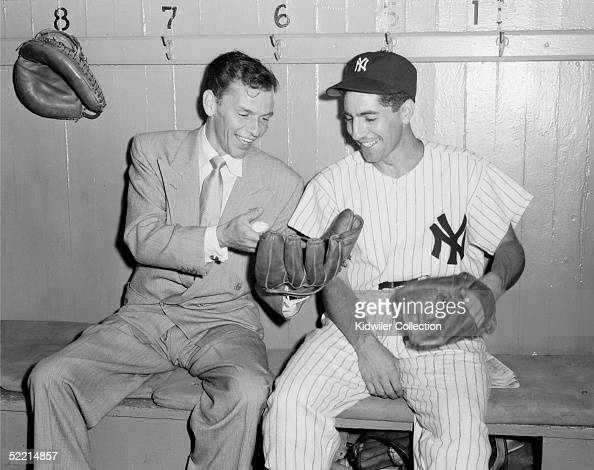 Crooner Frank Sinatra and Phil Rizzuto of the New York Yankees share a laugh in the Yankee dugout at Yankee Stadium in the Bronx New York Sinatra was...