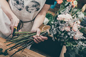 Crop woman in apron cutting stems of flowers creating beautiful bouquet in shop.