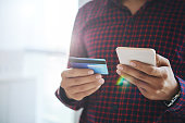 Close-up shot of faceless man in shirt doing purchase online via smartphone with help of credit card