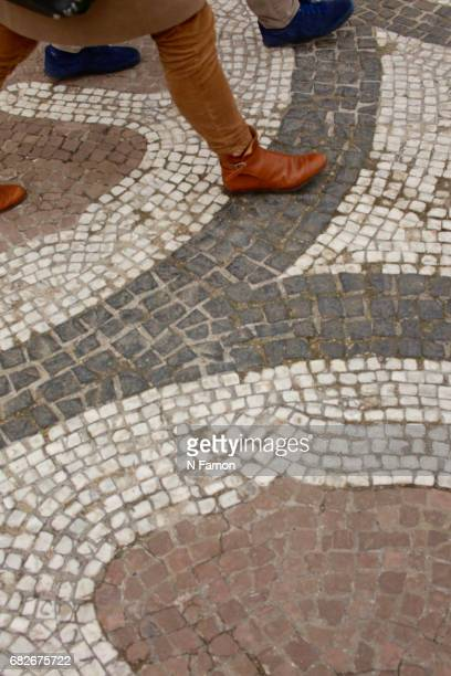 Crop of women walking over mosaic tiles.