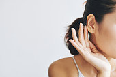 Crop female with dark hair in ponytail touching?ear with help of fingers and with tenderness on grey background
