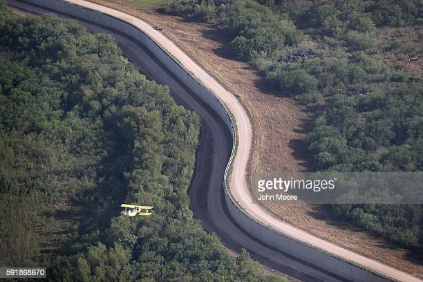 A cropduster flies near a border fence which helps secure the USMexico border on August 18 2016 near McAllen Texas USMexico border security has...