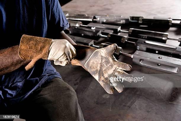 Cropped afrikanische amerikanischer Arbeiter Tragen von Handschuhen