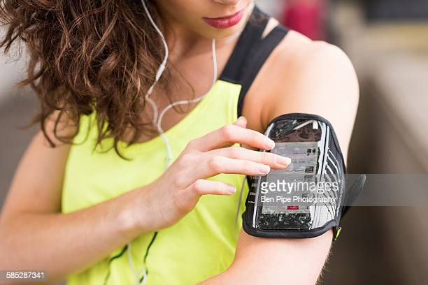 Cropped close up of female runner choosing music on smartphone armband