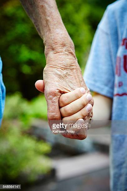Cropped close up of senior woman and grandson hands holding in park