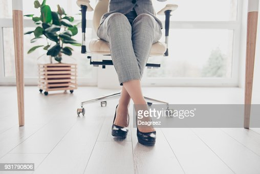 Cropped close up photo of healthy beautiful elegant woman's legs wearing high-heeled shiny black shoes, the woman is sitting in office at the table on modern luxurious armchair : Stock Photo
