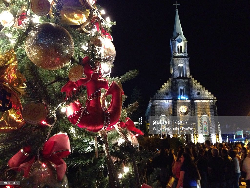 cropped decorated christmas tree against church at night stock