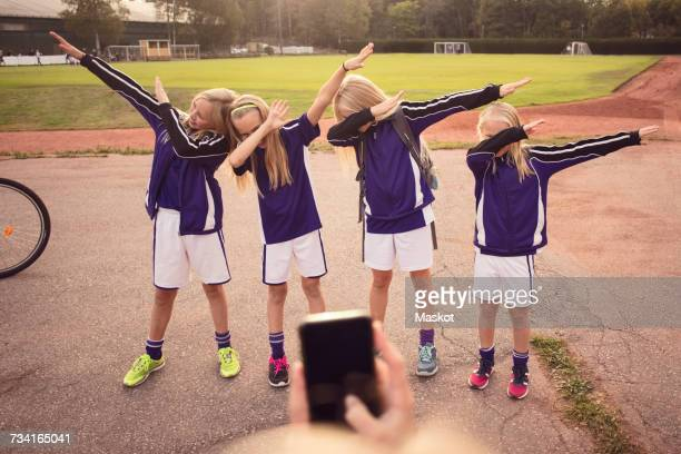 Cropped girl photographing friends performing dab dance on footpath against soccer field