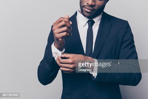 Cropped half face portrait of trendy, attractive, stunning man in black tuxedo with tie fasten button on sleeve cuffs of his white shirt, isolated on grey background : Stock Photo