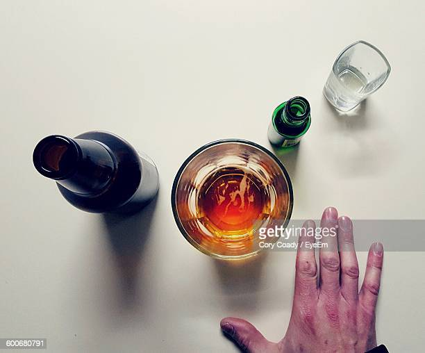 Cropped Hand By Beer Glass Against White Background