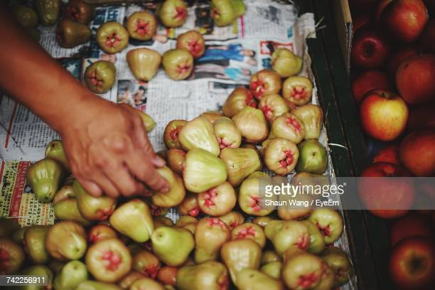 Cropped Hand Choosing Water Apples For Sale At Market