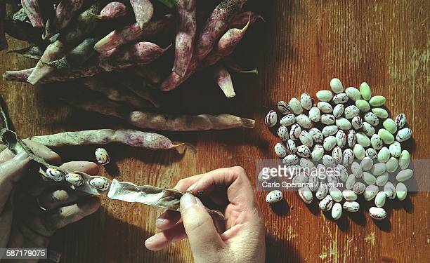 Cropped Hand Cleaning Beans On Table