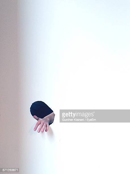 Cropped Hand Coming Out Through Hole On White Wall
