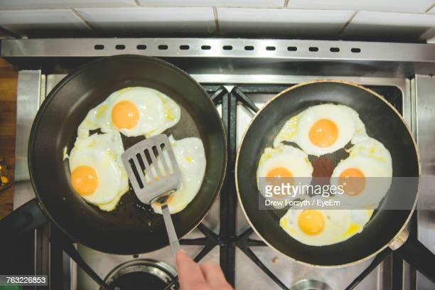 Cropped Hand Frying Eggs In Pan On Stove