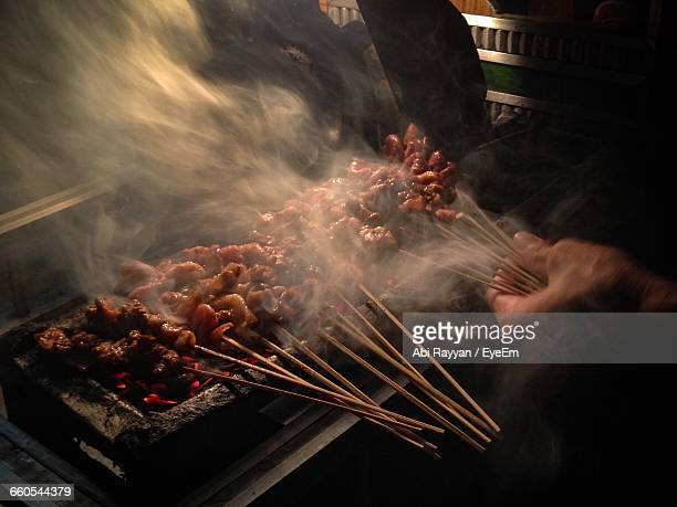 Cropped Hand Grilling Chicken Satay On Barbecue Grill