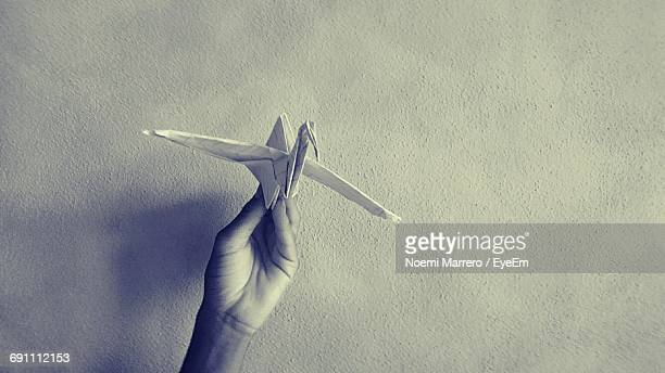 Cropped Hand Holding Bird Origami Against Wall
