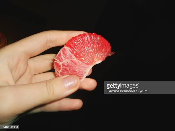 Cropped Hand Holding Blood Orange Over Black Background