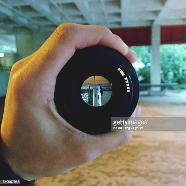Cropped Hand Holding Camera Lens With Woman Reflection In It