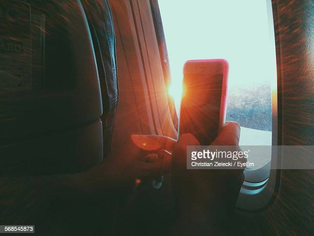 Cropped Hand Holding Cell Phone In Airplane By Window