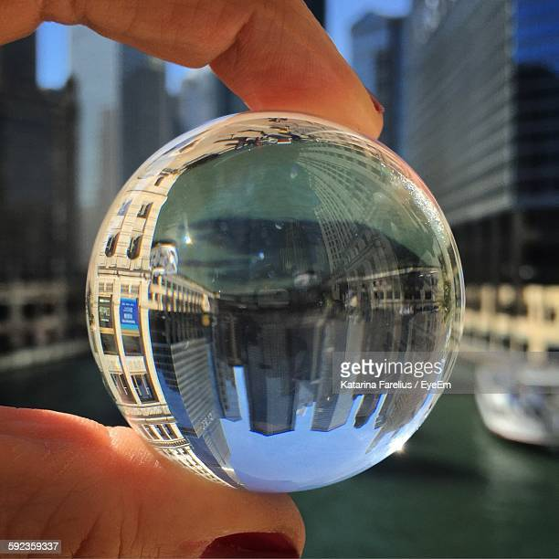 Cropped Hand Holding Crystal Ball Against City Buildings