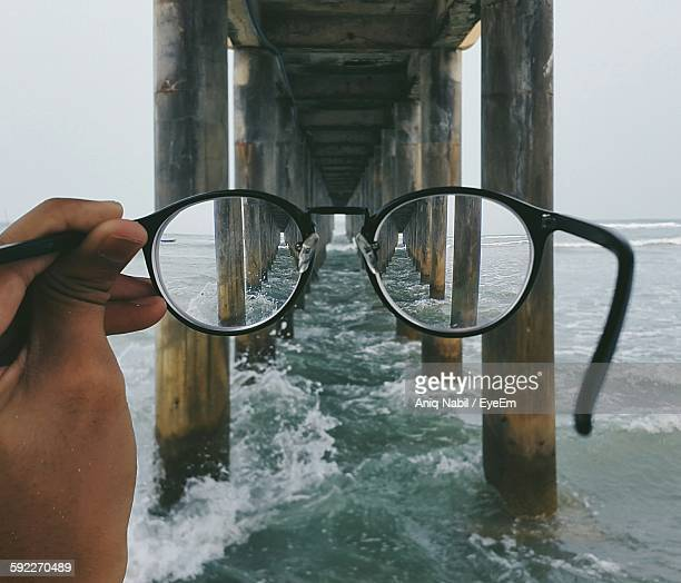 Cropped Hand Holding Eyeglasses Under Bridge On Sea