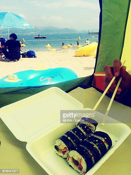 Cropped Hand Holding Gimbap Food Using Chopsticks In Tent