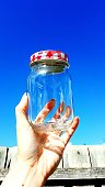 Cropped Hand Holding Glass Jar Against Clear Blue Sky