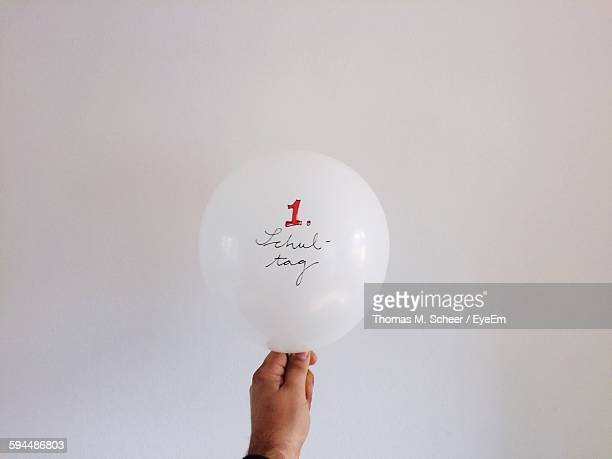 Cropped Hand Holding Helium Balloon With Text Against White Background