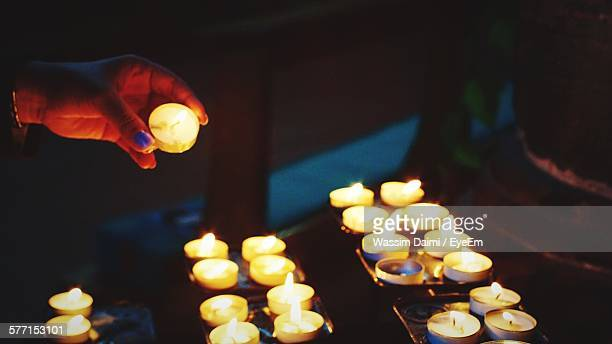 Cropped Hand Holding Lit Tea Light Candle
