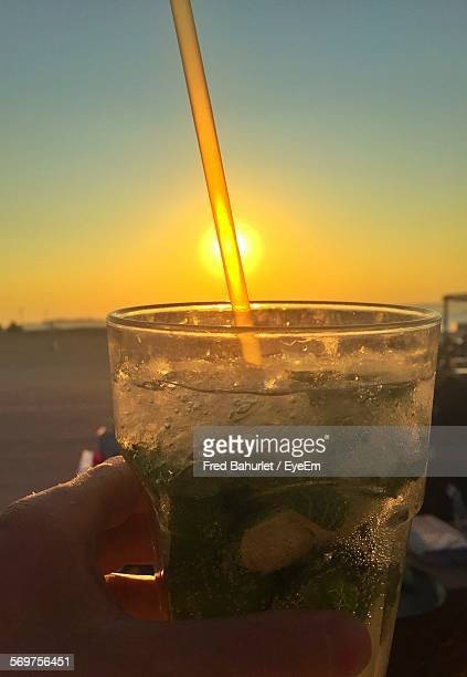 Cropped Hand Holding Mojito Against Clear Sky During Sunset