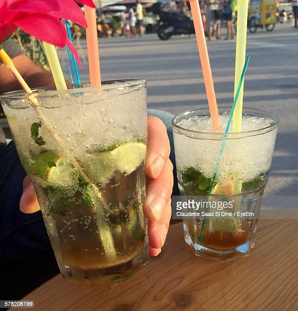 Cropped Hand Holding Mojitos On Table