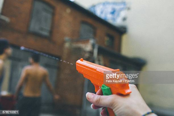 Cropped Hand Holding Orange Water Gun By Building