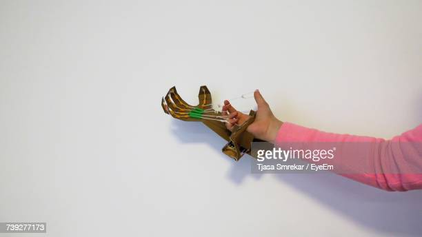 Cropped Hand Holding Paper Craft Product Against White Background