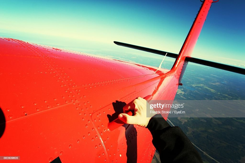 Cropped Hand Holding Red Airplane Handle Flying In Sky