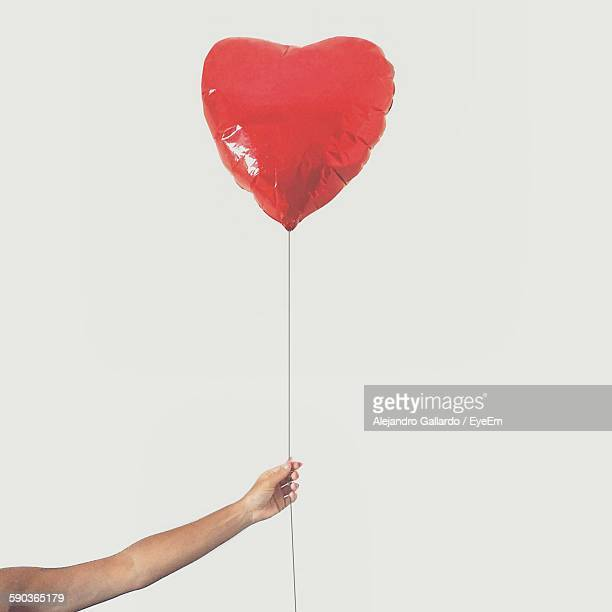Cropped Hand Holding Red Heart Shape Balloon Against Clear Sky