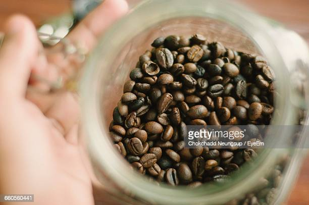 Cropped Hand Holding Roasted Coffee Beans Jar