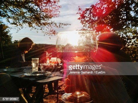 Cropped Hand Holding Wineglass At Outdoor Table On Sunny Day