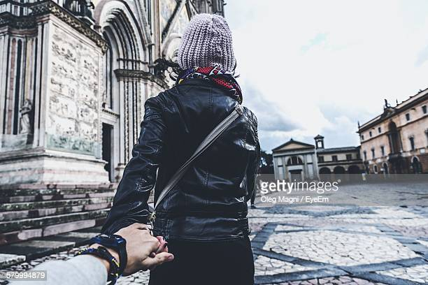 Cropped Hand Holding Woman Hand While Walking On Street Against Buildings