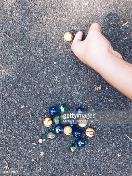 Cropped Hand Of Boy Playing Marbles On Footpath