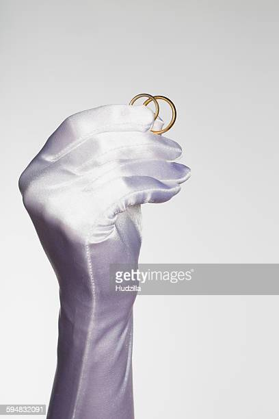 Cropped hand of bride holding wedding rings against white background