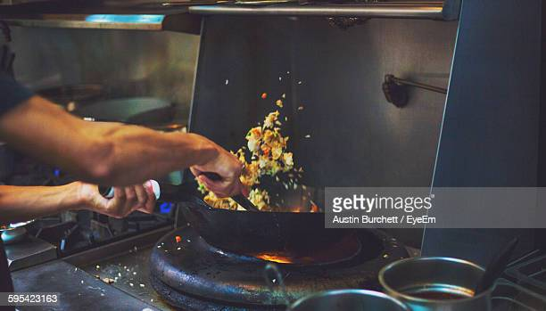 Cropped Hand Of Chef Cooking Food On Stove